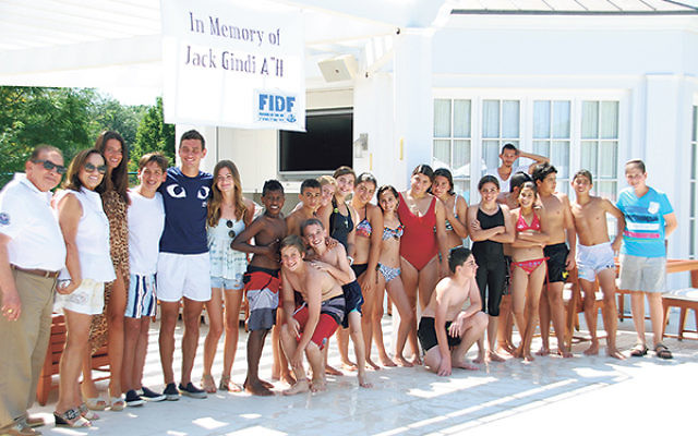 Members of the Sutton family, left, who hosted the kids in Deal, pose poolside with campers and counselors.