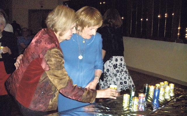 Holocaust survivors Tova Friedman, left, and Devorah Hilsenrath, both of Highland Park, light candles in memory of those lost in the Shoa.