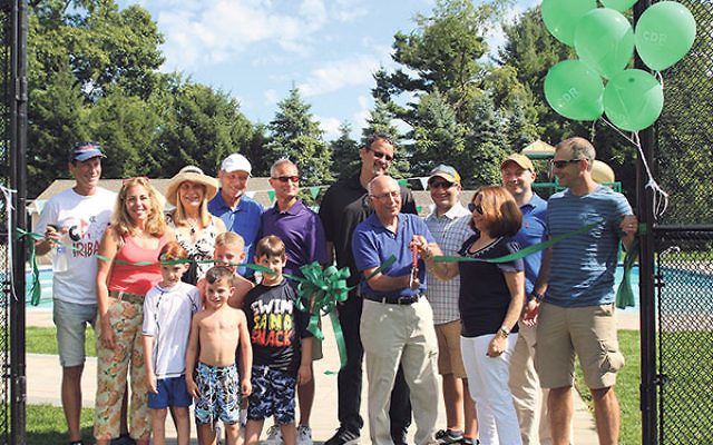 At the dedication of the Flo Peck Pool at Camp Deeny Riback are campers Ryan Strulson, front, and, from left, Seth Perlstein (grandson of the Seidens), Noah Stoch, and Tyler Feldman; and, from left, Mitchell, Valerie, Cindy, Martin, and Norman Riback; Fla