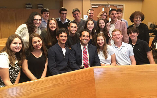 Names, Not Numbers creator Tova Fish-Rosenberg and reporter Jonah Kaplan gather with students after the program's opening session.