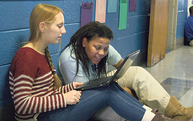 Helping students work on reading skills at Rise Academy in Newark.
