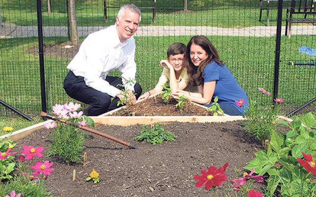 Above, Sam Epstein and his gardening assistants — parents Sheldon and Lisa — at the mitzva garden he's cultivating at Adath Shalom in Parsippany.