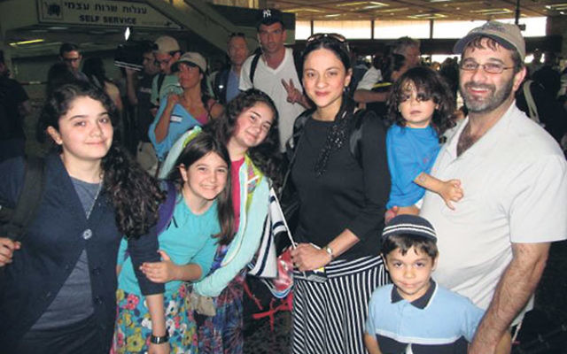 Kim and Mitchell German — with their children, from left, Sarah, Arielle, Yael, Yosef (being held by Mitchell), and Yehuda — at JFK International Airport as they make aliya to Israel. Despite the war with Hamas, Kim German said, she had &ldquo