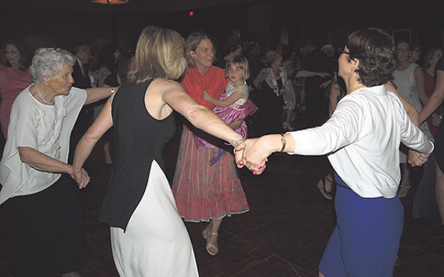 Paula Gottesman, far left, dancing at the gala with her daughter Sally (holding her daughter); Kim Hirsh, front, next to Gottesman; and others.