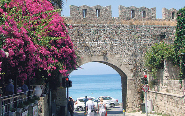 Tourists walking through the old city walls of Rhodes near the Square of Jewish Martyrs.