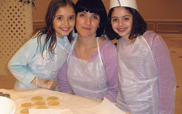 Masha Milman of Manalapan came with her daughters, Mishele, 10, on left, and Roshele, eight, to bake hamantaschen.