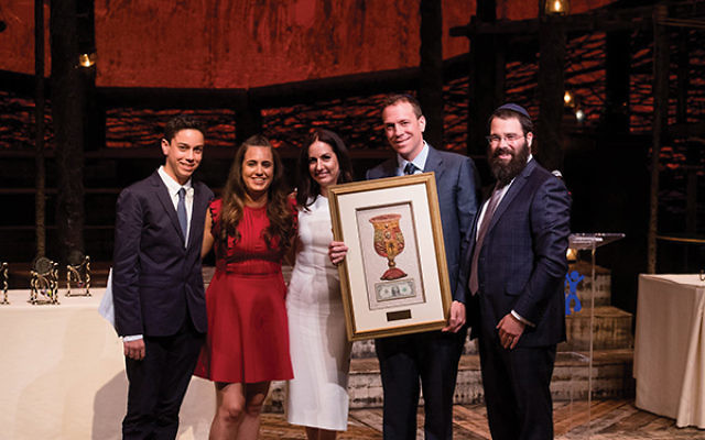 Accepting their Hand in Hand award from Rabbi Laibel Schapiro, far right, are, from left, Aidan, Harper, Ivy, and Russell Herman.
