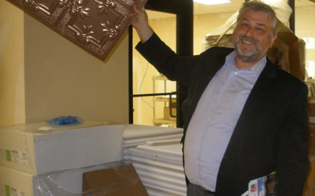 Rutgers Hillel executive director Andrew Getraer holds up a ceiling tile to be used in the new dining hall.