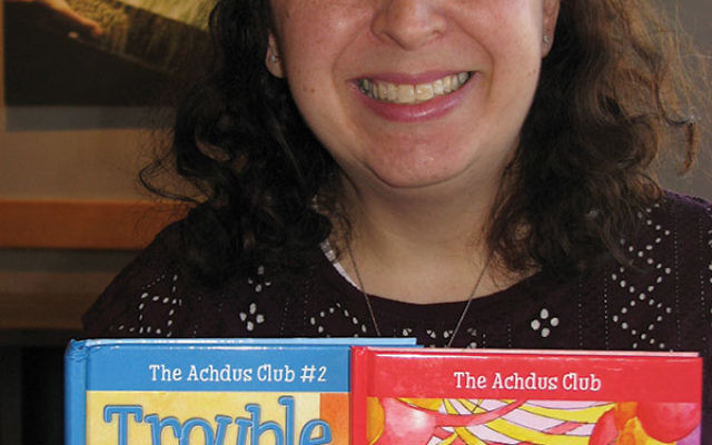 "Author Faygie Holt with The New Girl and Trouble Ahead, the first two books in her children's series ""The Achdus Club."""