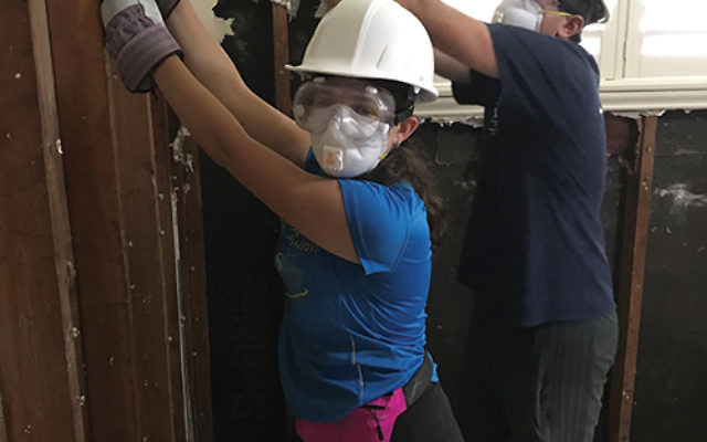 NCSY members Ben Josephson and Meira Book repair drywall at a damaged home in Houston. Photo by Rabbi Ethan Katz
