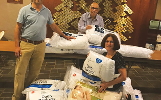 Temple B'nai Shalom in East Brunswick is collecting new wrapped pillows t for storm victims in Texas and Florida. From left are Rabbi Eric Eisenkramer, Barry Wechsler, and Dr. Iris Udasin. Photo courtesy Temple B'nai Shalom
