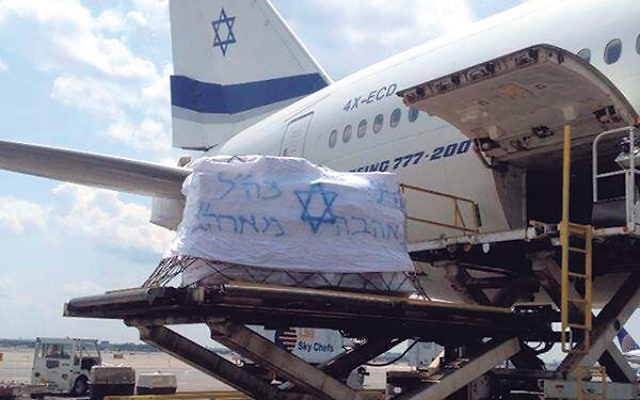 """A shipment of goods to IDF soldiers is loaded aboard an El Al plane. The banner reads: """"To the soldiers of the IDF with love from the United States of America."""""""