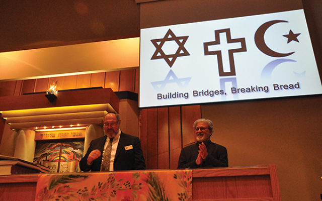 """Rabbi Eric Wisnia of Congregation Beth Chaim, and Khatib Monzoor Hussain of the Institute of Islamic Studies, greet attendees of the """"Building Bridges, Breaking Bread"""" program. Photos by Michele Alperin"""