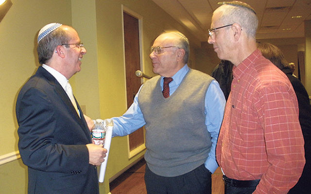 David Ze'ev Jablinowitz, left, chats with community members after the program at Congregation Ohav Emeth in Highland Park.