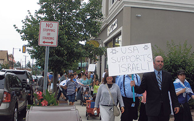 Central New Jersey Stands with Israel rally host Josh Fine is followed by supporters marching along Raritan Avenue in Highland Park.