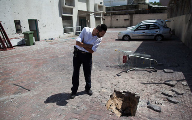 An Israeli inspects the damage from a Palestinian rocket strike outside a store in the southern Israeli city of Ashdod, July 9, 2014.