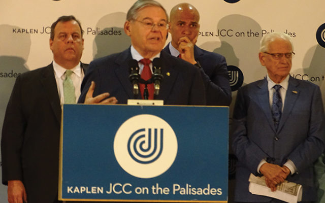 """""""Together the collective glow of our humanity will cast a light on the darkness of those who hate,"""" said Sen. Robert Menendez; behind him are, from left, Gov. Chris Christie, Sen. Cory Booker, and Rep. Bill Pascrell. Photos by Robert Wiener"""
