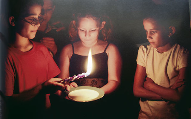 Concluding its look back over a century of trauma and triumph, the JDC's new book ends with a picture of Cuban children performing the Havdala ceremony in 2009.