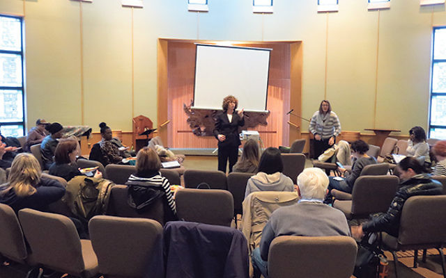 Suzanne Groisser, coordinator of legal services at the Rachel Coalition, left, and Sara Mendez Emma, clinical coordinator of child and adolescent services at Jewish Family Service of MetroWest, instruct a class of volunteers training to become members of