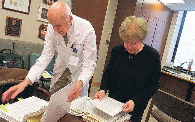 Surgeon Victor Parsonnet and Linda Forgosh, executive director of the Jewish Historical Society of New Jersey, examine some of the papers he is donating to JHS.