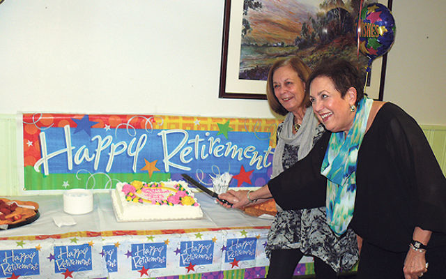 Outgoing co-executive directors of JVS Caren Ford, left, and Nancy Fisher cut the cake at their retirement party in mid-March.