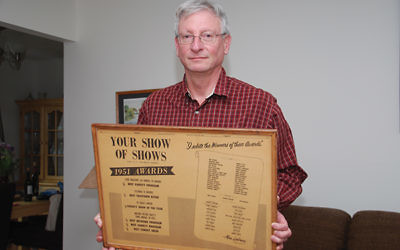 """Barry Jacobsen, former assistant to """"Your Show of Shows"""" producer Max Liebman, holds a promotional poster for the popular program."""