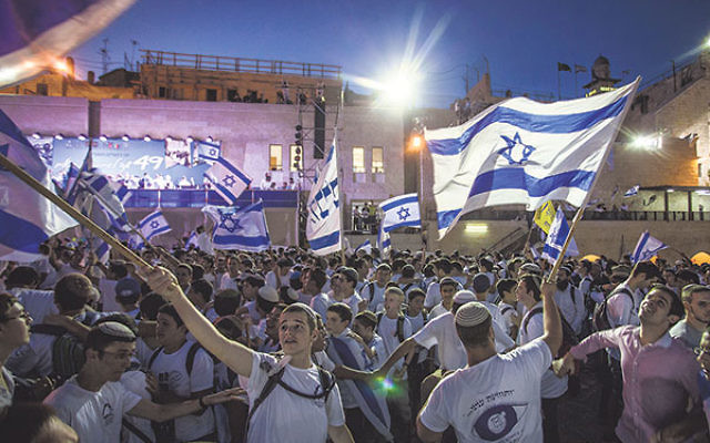 Jewish boys waving Israeli flags near the Western Wall in the Old City of Jerusalem as part of celebrations for Jerusalem Day, June 5.
