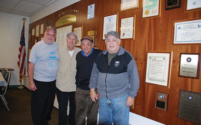 Post 972 leaders, from left, Jack Small, Tom Renna, Bernie Rothenberg, and Bob Schwartz, in front of the post's Wall of Honor in the JWV room at Marlboro Jewish Center. Photo by Alan Richman