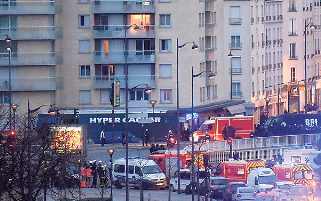 Police arrive at the Hyper Cacher kosher market, where the hostages were being held, Jan. 9.