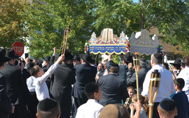 Hundreds accompanying the new Torah scroll danced and sang through Highland Park.