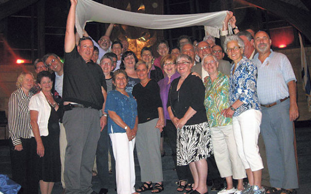 """Members of New Jersey's Lesbian & Gay Havurah stand under a huppa held by members of Temple Emanu-El in Edison to celebrate the """"marriage"""" of the two before the synagogue's annual Gay Pride Shabbat in June 2011."""