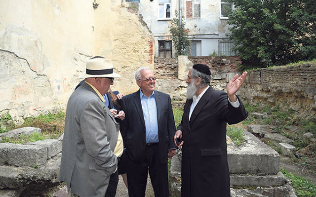 Meylach Schochet, a leader of the Jewish community in Lviv, right, stands beside Larry Lerner, center, and Rutgers University professor Stephen Bronner in the ruins of the Golden Rose Synagogue, which Schochet hopes to rebuild.