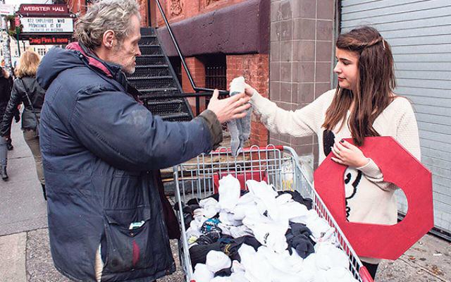 Adina Lichtman gives socks she has collected through Knock Knock Give a Sock to a homeless man in New York City.
