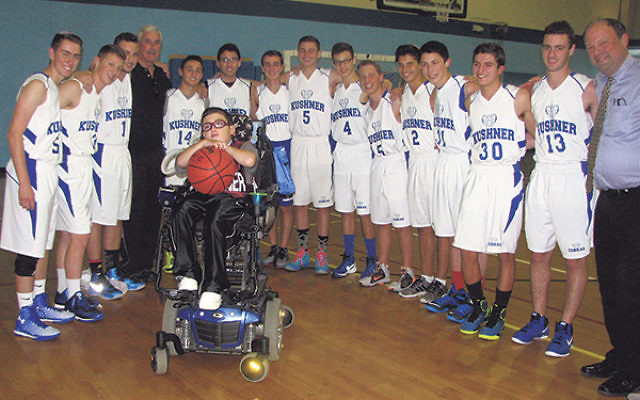 Lucas Reiling holds the ball, surrounded by his Kushner Pythons teammates, including Rabbi Richard Kirsch, far right, and coach Jan Sandusky, fourth from left.