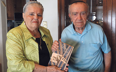 Luna Kaufman presents fellow survivor Naftali Laks with a copy of her memoir, Luna's Life, during their Sept. 4 meeting.