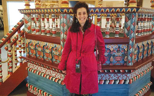 During a visit to trace her family roots in Poland, Lynne Azarchi stands in front of a reconstructed wooden synagogue in Warsaw's POLIN Museum of the History of Polish Jews.