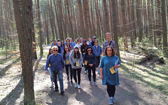 "Survivor Michael Zeiger, front, left, and other March of the Living participants walk through the ""Killing Forest,"" Lopuchowo Forest in Tykocin, Poland, where some 2,000 Jewish men, women, and children — almost all the Jewish inhabitants"