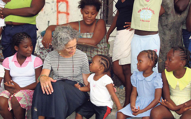 """Ruth Messinger — here visiting a local literacy NGO at a tent camp in Haiti two years after the 2010 earthquake — says AJWS acts on the principle that """"the problems of marginalized people are issues with which Jews need to be concerned.&"""