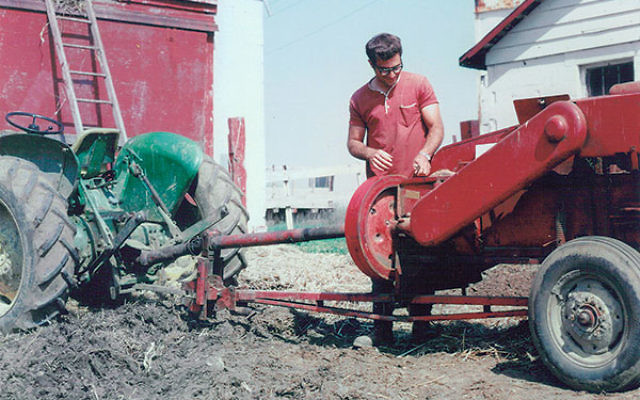 Micha Livne repairs a hay baler while serving as a shaliah on the Hechalutz Farm in the late '60s.