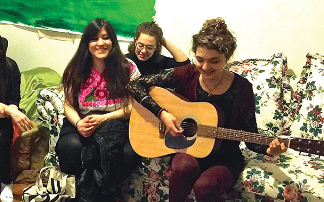 Eva Meiling Pollitt performs an ode to her mouse roommates during the Shabbat dinner held by Ronit Levy Delgado, left, who painted the bucolic scene to set a picnic mood. Photo by Amy Sara Clark/JW
