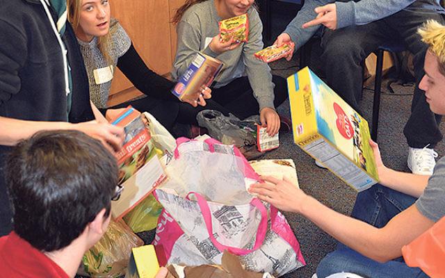 On Mitzva Day, the Sandy Senior Fellows helped organize a food drive; from left, Sawyer Malkin, Paul Gurman, Emily Esquenazi, Jen Koppel, and Matt Fryfield.