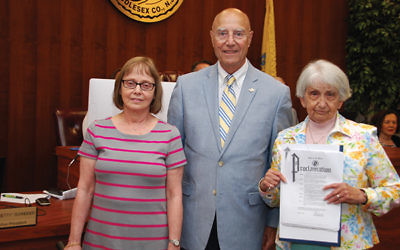 Monroe Township Mayor Gerald Tamburro is flanked by Karen Mandel, on left, and Marilyn Gerstein, who is holding the proclamation condemning anti-Semitism. Photo by Alan Richman