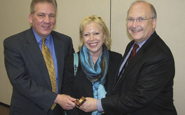 Incoming NJJN president Rob Daley, left, receives the gavel from his predecessor, Phil Litwinoff, and former president Linda Levi.