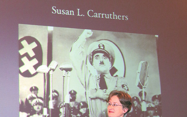 Susan Carruthers, a professor of history at Rutgers-Newark, seated below a poster for The Great Dictator, Charlie Chaplin's satirical 1940 film portrait of Adolf Hitler. Carruthers said the Production Code, which laid out strict regulations