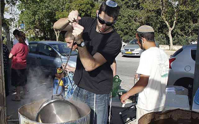 Residents get their cooking pots dipped into hot water in preparation for Passover in Efrat, a Jewish settlement in the West Bank.