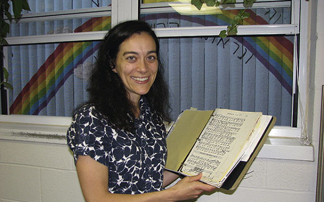 In her office at Morristown Jewish Center Beit Yisrael, Cantor Shana Onigman displays a book of old sheet music; she painted the brick wall outside her window with a blue sky, a rainbow, and a quote from parshat Noach.