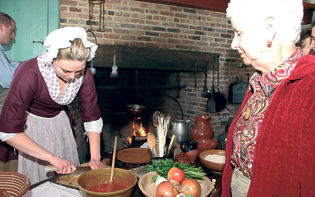 Chef Sarah L. chops onions to make albondigas, a Sephardi meatball recipe, as Leila Sulkes of Freehold looks on.