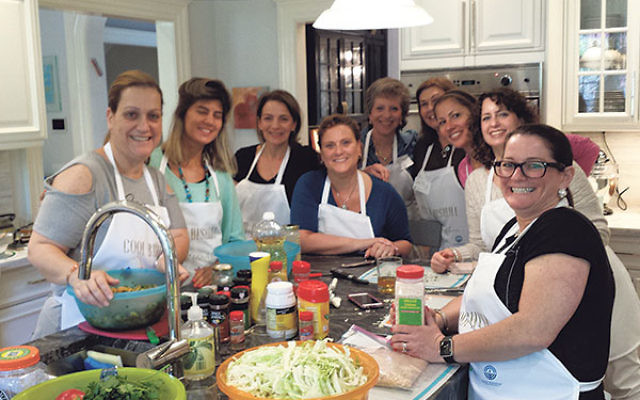 Osi Lankri and her assistant Mor Bohadana, left, create an Israeli meal in a Short Hills home; with them are, from left, host Robin Buchalter, Beth Levin, Eileen Breindel, Catalina Silberman, Philippa Miller, Stephanie Evenchick, and Debbie Zucker.