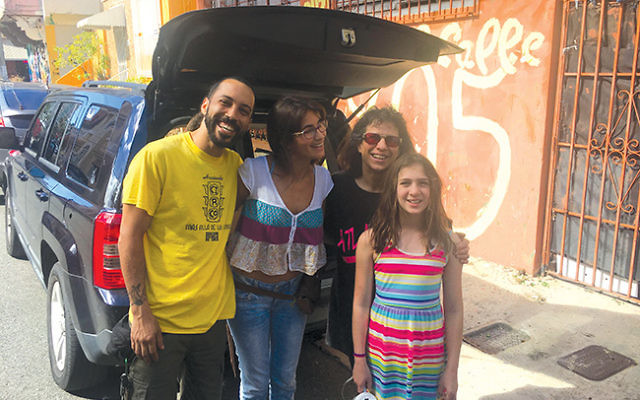 Julie Meyers, at right, with Dylan Meyers, and staff members of the Social Circus of Puerto Rico in front of an open trunk loaded with donated items collected in New Jersey. Photo by Karin Meyers