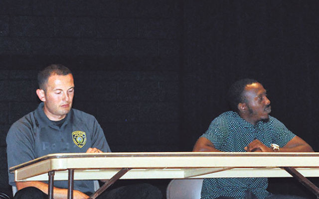 "At a July 27 gathering in Princeton, police officer Bill Kieffer, left, said training of officers about racial profiling and cultural diversity is critical; Tone Bellamy told the gathering, ""It is not normal for a black man and a white cop to feel c"